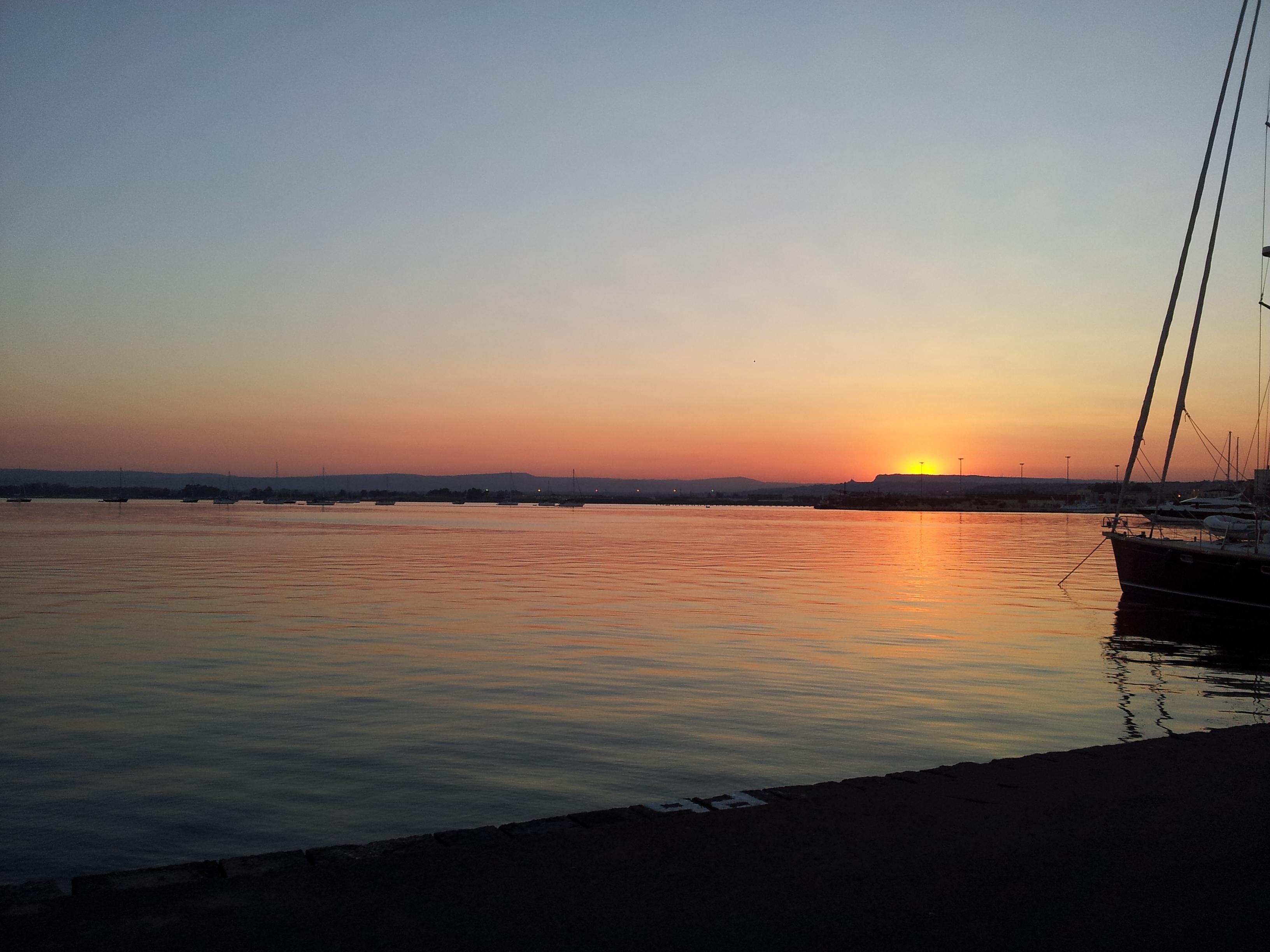 esplosioni di colori del Sole appoggiato sulle contrafforti dei  Climiti e che si riflettono sul mare liscio come l'olio del Porto Grande a Siracusa